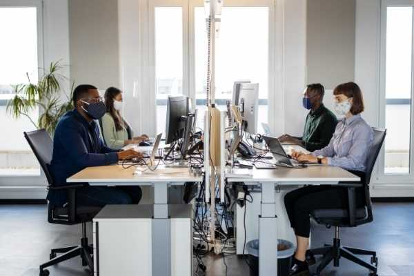Office setting with employees socially distanced and wearing masks